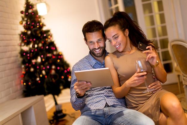 Knap jong paar die met tablet oudjarenvooravond winkelen