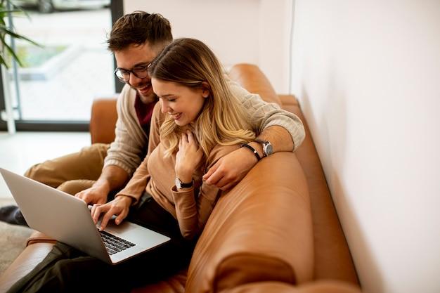 Knap jong stel met behulp van laptop samen zittend op de bank thuis