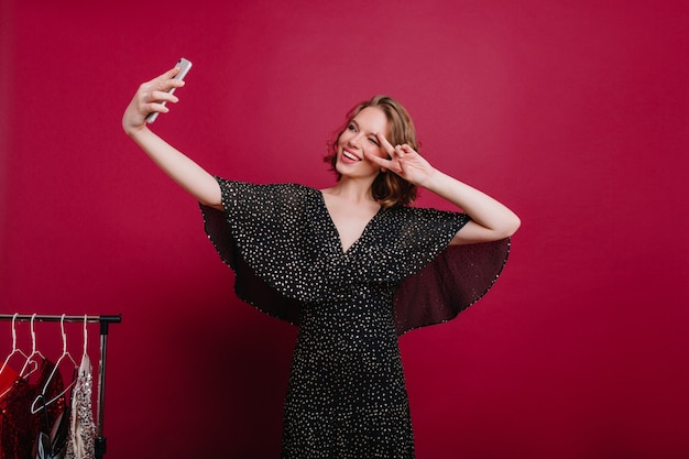 Knap jong vrouwelijk model met tatoeage die foto van zichzelf in de kleedkamer