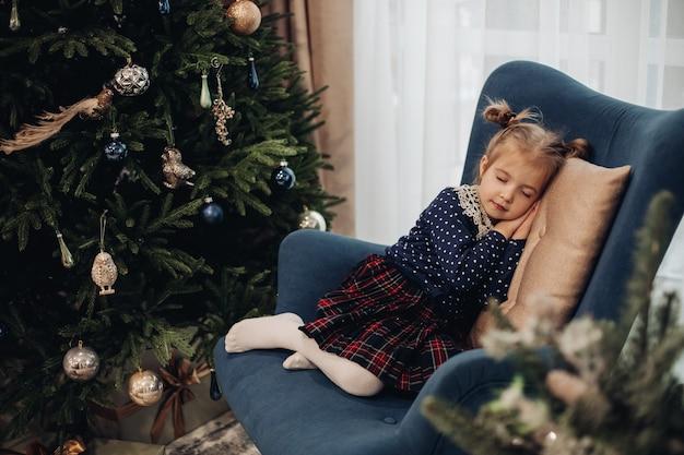 Knap kaukasisch kind in een jurk slaapt in de buurt van de kerstboom op een blauwe fauteuil thuis
