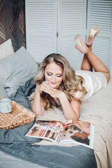 Knap kaukasisch meisje met donker krullend haar ligt in de grote lichte slaapkamer en leest een tijdschrift