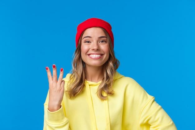 Knap kaukasisch vrouwtje in rode muts en gele hoodie, met nummer drie en glimlachend, bestelling of reservering, staand trots en opgetogen,