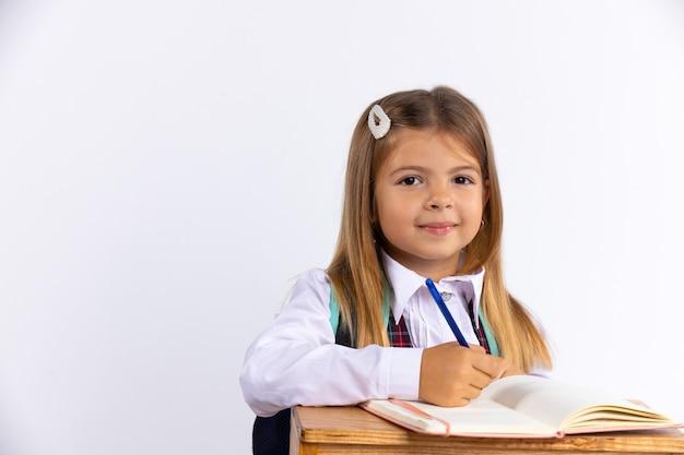 Knap klein meisje in schooluniform zit aan bureau geïsoleerd, witte muur met vrije ruimte. gelukkigste schoolmeisje dat huiswerk maakt. onderwijs concept.