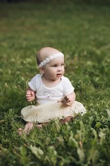 Knap klein meisje met kort blond haar en mooie glimlach in witte jurk zit in de zomer op een gras in het park en glimlacht