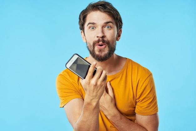 Knap mannelijk model met baard met een telefoon die binnen stelt
