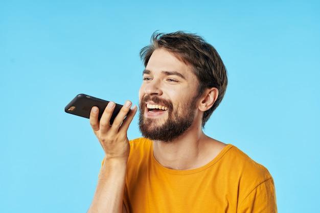 Knap mannelijk model met baard met telefoon het stellen in studio