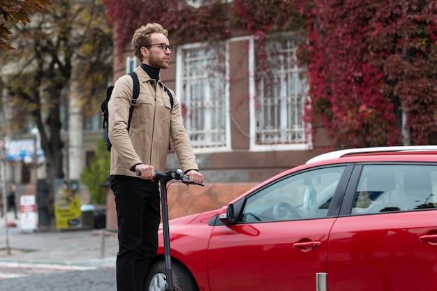 Knap mannetje dat een elektrische autoped berijdt