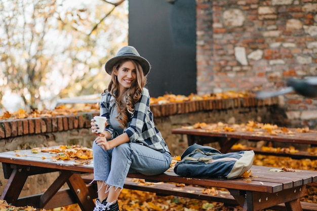 Knap meisje in korte denim broek zittend op een houten tafel in de herfst park