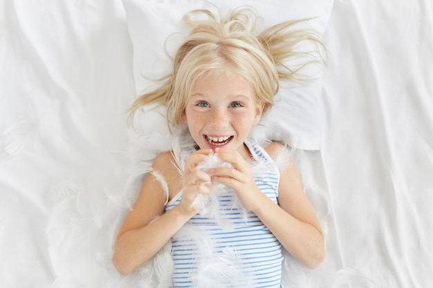 Knap meisje met sproeten die met haar broer bij bed spelen, met hoofdkussens vechten, veren vangen, gelukkige uitdrukking hebben. het sproeten van de blonde meisje het spelen met veren die op wit hoofdkussen op bed liggen
