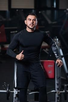 Knap met grote spieren in zwarte kleding toont een goed humeur