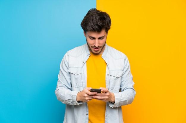 Knap over geïsoleerd kleurrijk verzendend een bericht met mobiel