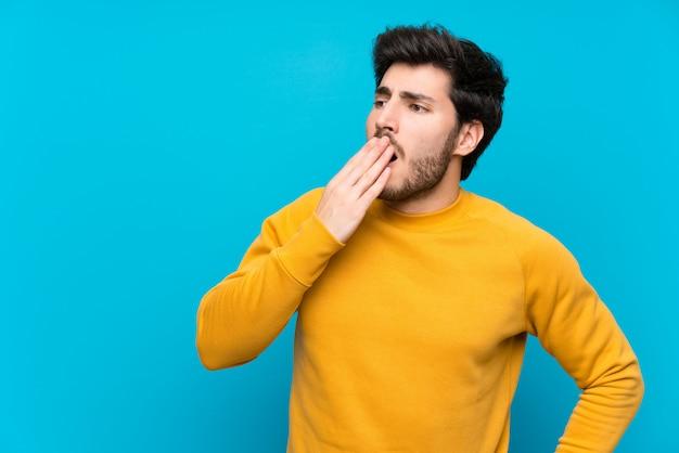 Knap over geïsoleerde blauwe muur die en wijd open mond geeuwen behandelen met hand
