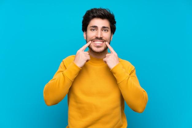 Knap over geïsoleerde blauwe muur die met een gelukkige en prettige uitdrukking glimlacht