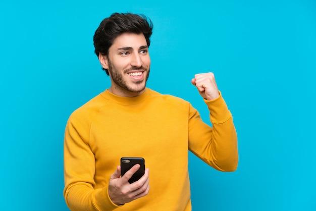 Knap over geïsoleerde blauwe muur met telefoon in overwinningspositie