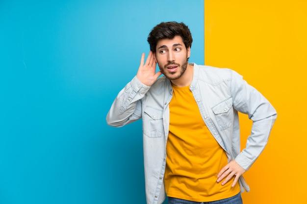 Knap over geïsoleerde kleurrijke achtergrond die aan iets luistert door hand op het oor te zetten