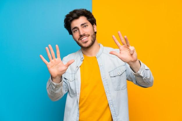 Knap over geïsoleerde kleurrijke muur die negen met vingers tellen