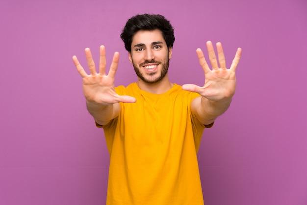 Knap over geïsoleerde purpere muur die tien met vingers tellen