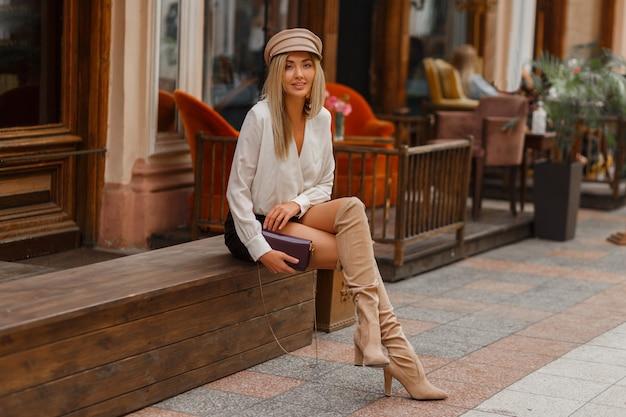 Knap sexy blond model in witte blouse en leren skrt en gebreide blokdijhoge laarzen in beige