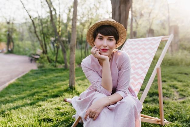 Knap stijlvolle jonge vrouw in ouderwetse hoed zittend op fauteuil te wachten op picknick