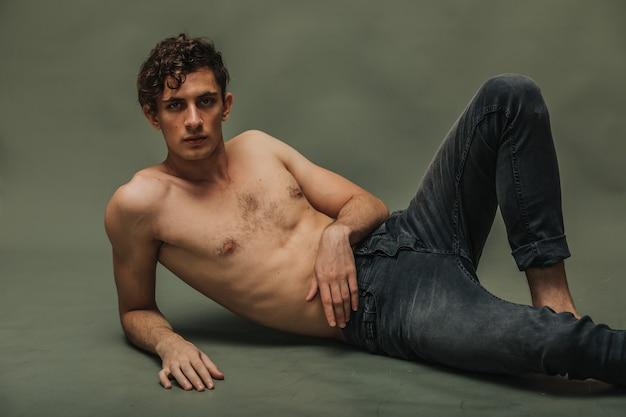 Knap topless mannelijk model dat op de groenboekvloer ligt