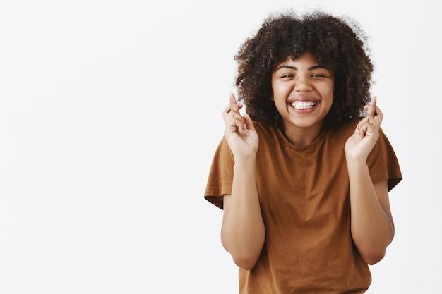 Knap, trouw en optimistisch tiener afro-amerikaans meisje met afro kapsel vingers gekruist voor geluk en glimlachend vreugdevol biddend om een droom die uitkomt of een wens doet