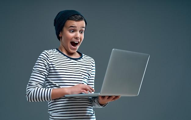 Knap verrast stijlvolle jongen in een gestreepte trui en hoed met een laptop in de hand geïsoleerd op grijs.