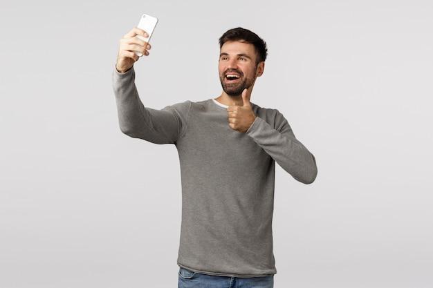 Knap vriendelijk en extravert kaukasisch mannetje in grijze sweater die selfie nemen