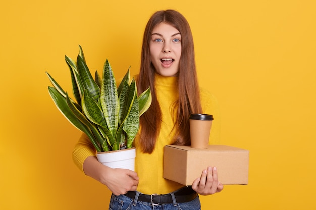 Knap vrouwtje met lang steil haar poseren binnenshuis met haar staf in handen: bloempot, kartonnen doos en afhaalkoffie. fascinerende vrouw met verbaasde gezichtsuitdrukking, met open mond.