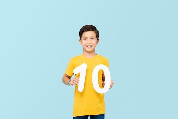 Knappe 10 éénjarigen gemengde rasjongen die en aantallen geïsoleerd glimlacht houdt