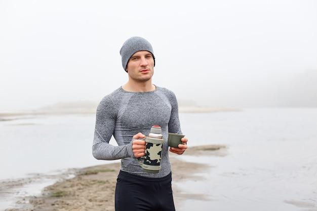 Knappe aantrekkelijke man aan de oever van de rivier, poseren met thermos in de buurt van prachtige mistige meer, vooraanzicht van peinzende man genieten van warme koffie of thee, het dragen van pet