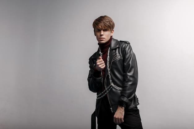 Knappe aantrekkelijke man in een zwarte trendy jas in retro stijl met een kapsel in rode golf en een zwarte broek met een zilveren ketting, poseren in een studio in de buurt van een witte muur. moderne stijlvolle man