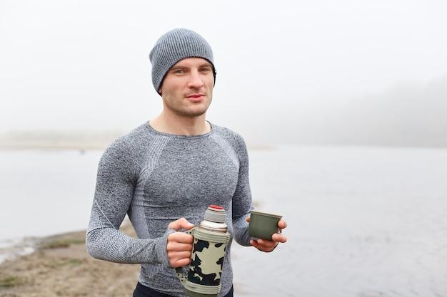 Knappe aantrekkelijke man op de oever van het meer met mistige rivier