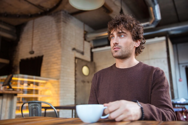 Knappe aantrekkelijke peinzende gekrulde nadenkende man in bruine sweetshirt die koffie drinkt terwijl hij in café zit