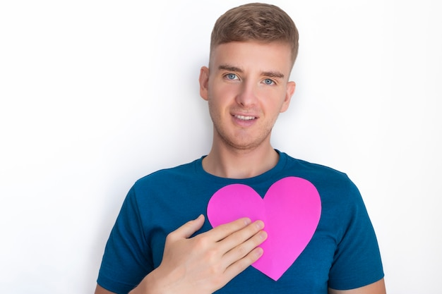 Knappe aardige vent houdt, houdt valentijn op borstniveau, jonge man met valentijnskaart, rood of roze wenskaart in een vorm van een hart. kopieer ruimte. fijne valentijnsdag. gevoelens, liefde, relatiesconcept