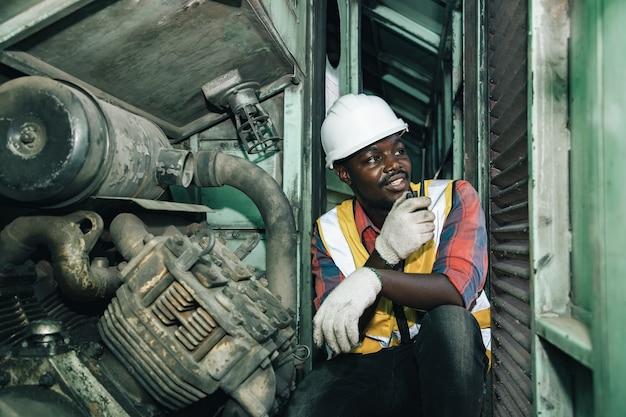 Knappe afrika-amerikaanse industriële engineering zijn plannen en bespreken motoren in garagefabrieken in treinstations met walkie takie