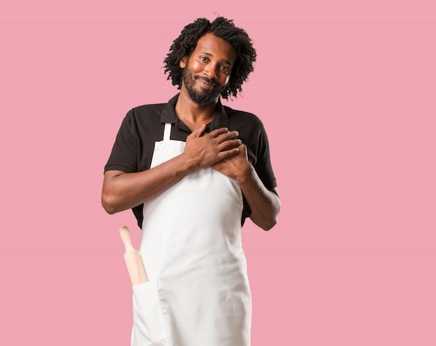Knappe afrikaanse amerikaanse bakker die een romantisch gebaar, in liefde met iemand doet of affectie voor één of andere vriend toont