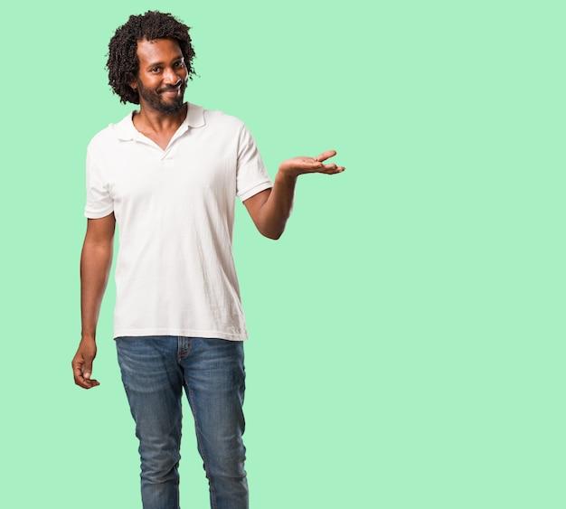 Knappe afrikaanse amerikaanse holding iets met handen, die een product toont, glimlachend en vrolijk, die een denkbeeldig voorwerp aanbiedt