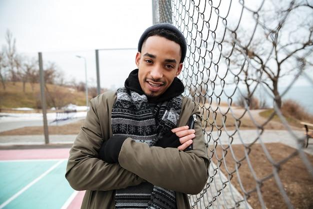 Knappe afrikaanse amerikaanse jonge mens die zich met in openlucht gekruiste wapens bevinden