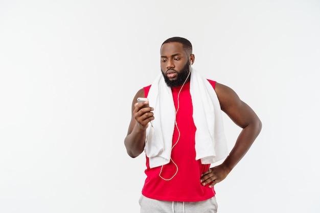 Knappe afrikaanse amerikaanse mens het luisteren muziek op zijn mobiel apparaat na sportoefening.