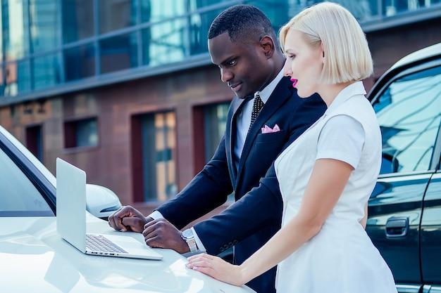 Knappe afrikaanse, amerikaanse zakenman in een stijlvol zwart pak en aantrekkelijke blonde vrouw zakelijke dame staan in de buurt van een dure auto en werken met een laptop. auto aankoop en verhuur concept