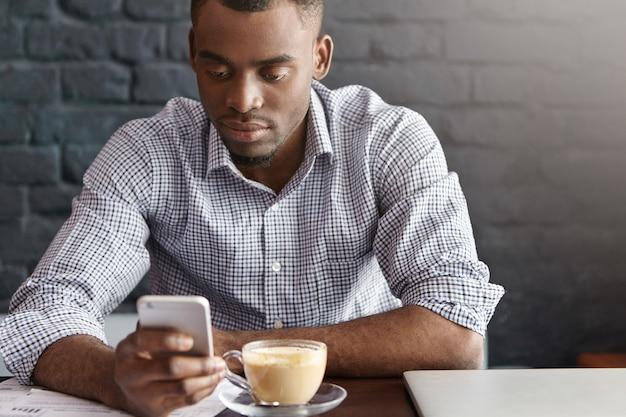 Knappe afrikaanse beambte draagt een geruit overhemd met opgerolde mouwen en geniet van online communicatie