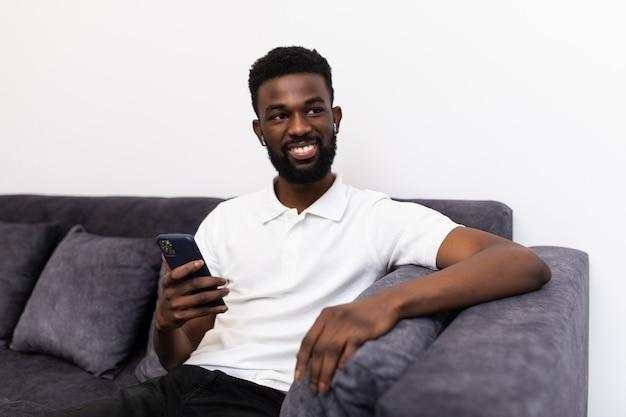Knappe afrikaanse man bellen via airpods zittend op een bank in zijn woonkamer