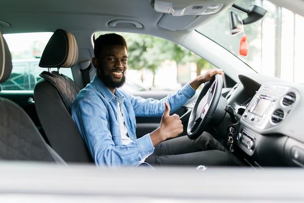 Knappe afrikaanse man duimen opdagen in auto