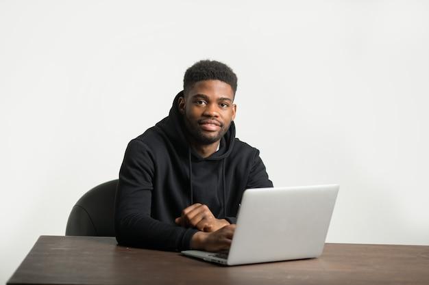 Knappe afrikaanse man in een trainingspak zit aan een tafel met een laptop