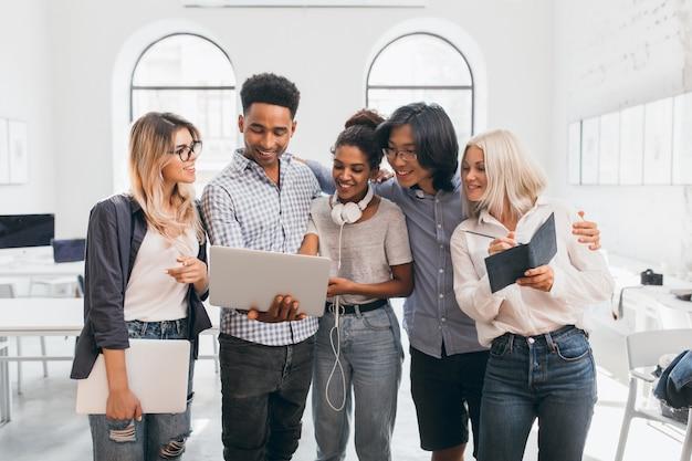 Knappe afrikaanse man in zwarte spijkerbroek met laptop en collega's presentatie tonen. indoor portret van aziatische man in glazen blonde vrouw omarmen en poseren met andere werknemers.