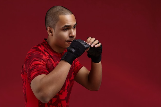 Knappe afrikaanse man met zwart lederen vingerloze handschoenen trainen in de sportschool, bezig met ponsen techniek, moe en uitgeput voelen. jonge donkere vechter met sterke armen boksen in studio
