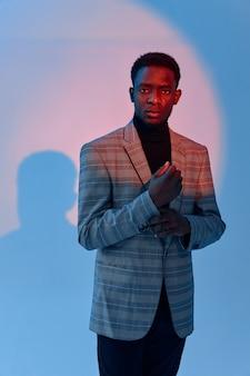 Knappe afrikaanse man pakken met zijn mouw studio neon
