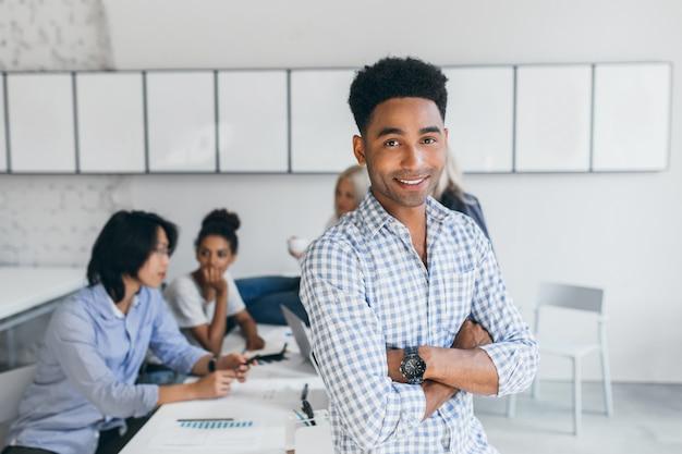 Knappe afrikaanse man zittend op tafel in kantoor terwijl zijn ondergeschikten werken aan nieuwe verkoopstrategie. indoor portret van zakenmensen van internationaal bedrijf poseren tijdens het werkproces.