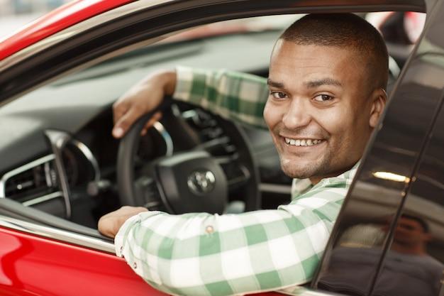 Knappe afrikaanse mannelijke bestuurder die aan de camera glimlacht, die in zijn nieuwe auto zit.