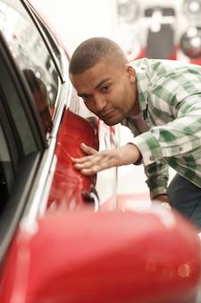Knappe afrikaanse mens die auto's onderzoeken bij het handel drijven, wat betreft deur van een auto.